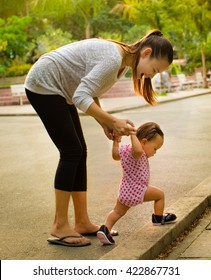 Mother teaches her baby daughter how to walk on a nice afternoon