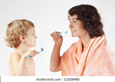 Mother teaches her little son to brush their teeth on a white background