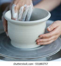 Mother teaches son to work on pottery wheel. Close up of dirty hands sculpting clay.