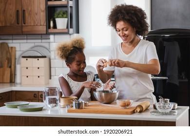 Mutter lehrt Kind Kochen und Hilfe in der Küche. Afroamerikanische Mutter und Tochter backen zu Hause.