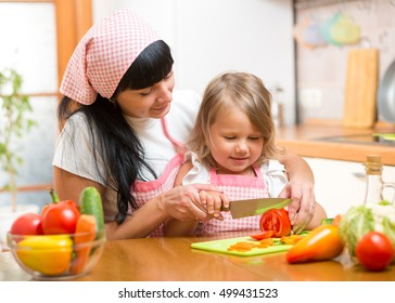 Mother teaching child making salad in kitchen. Mom and kid chopping vegetable on cutting board with knife. Cooking concept of happy family preparing food for dinner.