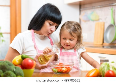 Mother teaching child making salad in kitchen. Cooking concept of happy family preparing food for dinner.