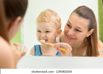 Mother teaching child teeth brushing. Mom cleaning son's teeth and looking at mirror reflection