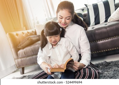 Mother Teaching children to do their homework at home,Asian family is happy