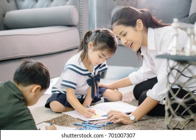 Mother Teaching children to do their homework at home ,and relax with they son to do home work by draw and paint, family , kid , education concept.