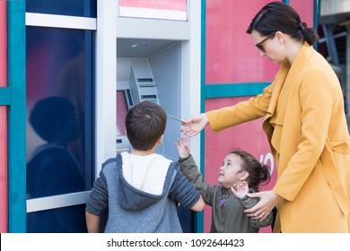 Mother teaching children to withdraw money from ATM machine. Small kids and their mother inserting credit card into ATM and taking money from the bank.