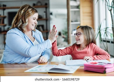 mother teaching daughter and helping with homework at home, son giving high five to mother