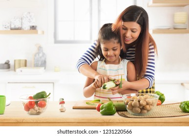 Mother teaching daughter how to peeling cucumber in kitchen