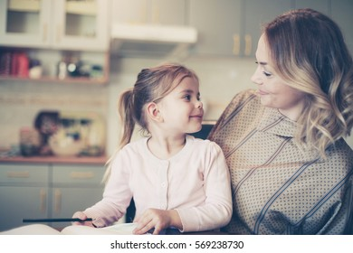 Mother teaching daughter how to write.  Looking each other.