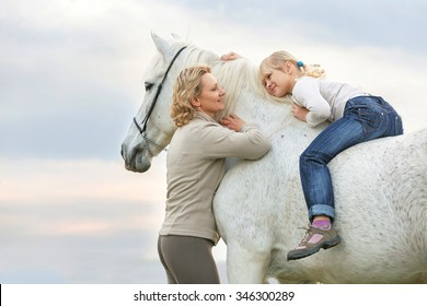 Mother teaching daughter to ride a horse.