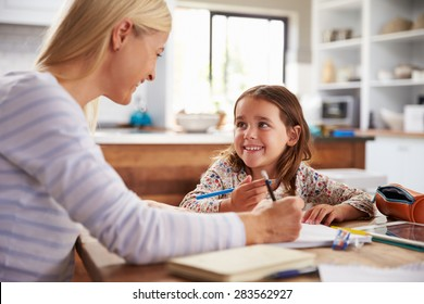 Mother teaching her daughter at home