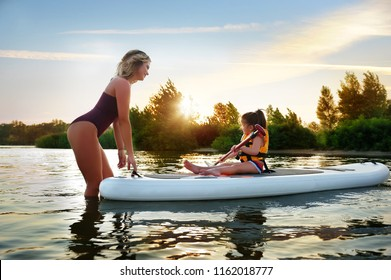 Mother teaching her daughter to paddle on the sup board against sundown