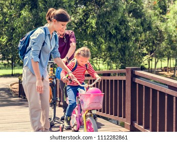 Mother teaching her daughter to ride a bike