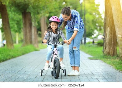 Mother teaching her daughter to ride bicycle in park on sunny day