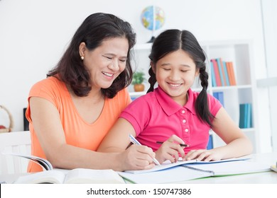 A mother teaching her daughter to write in the correct way at home