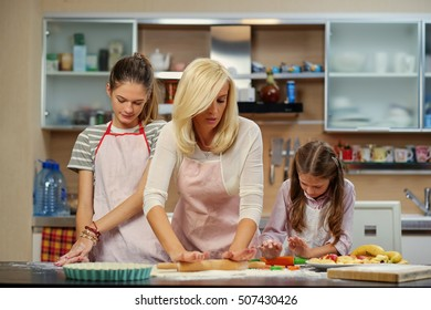 Mother teaching her daughters how to prepare the dough.