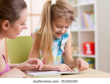 Mother teaching her kid daughter to read