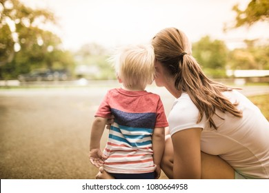 Mother teaching and her little boy outdoors.  Happy family and parenting concept.