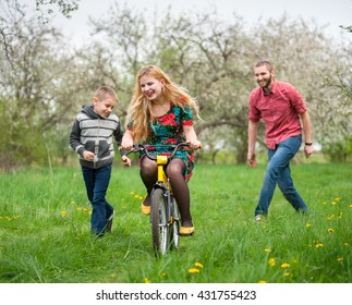 Mother teaching his son to ride a bike by his example in spring garden. Family having fun, female riding on children's bicycle. Man and a boy supporting her