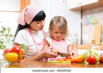 Mother teaching kid making salad in kitchen. Mom and child chopping vegetable on cutting board with knife. Cooking concept of happy family preparing food for dinner.