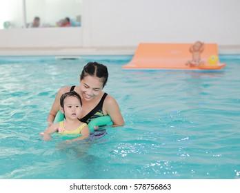 Mother teaching kid in swimming pool