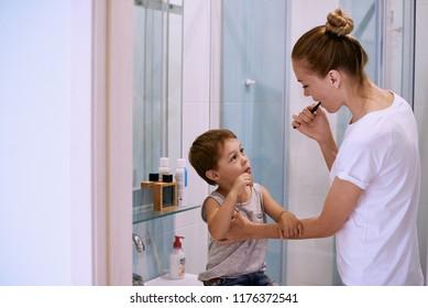 mother teaching kid teeth brushing at home