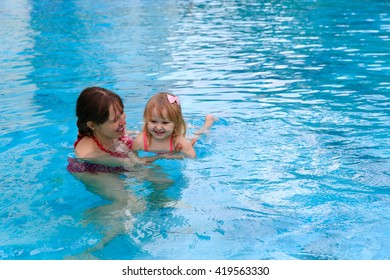mother teaching little daughter to swim