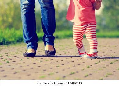 mother teaching little daughter to walk in summer park