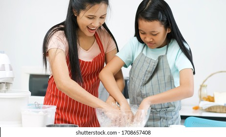 Mother teaching preteen daughter cooking bread in kitchen at home.family happy time.quarantine activity when outbreak of coronavirus