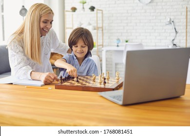 Mother teaching son to play chess following online lesson on laptop at home. Parent and child playing board game