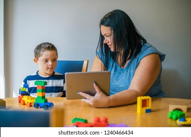 Mother teaching son from a tablet