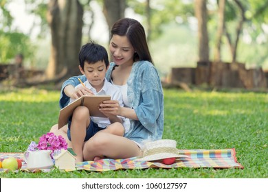 Mother teaching son write on notebook and sitting picnic in the park.