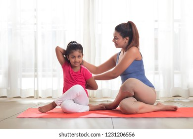 Mother teaching yoga to her daughter
