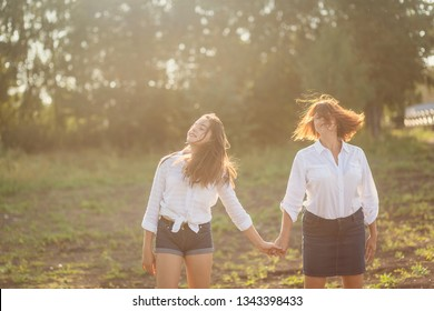 mother and teen daughter holding hands outdoors in summer