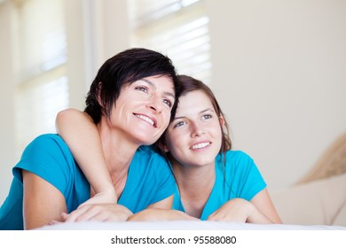 mother and teen daughter lying on bed and looking into distance