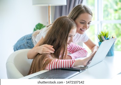 Mother and teen daughter using a laptop searching hotel room for the holidays best offers via internet buying online.