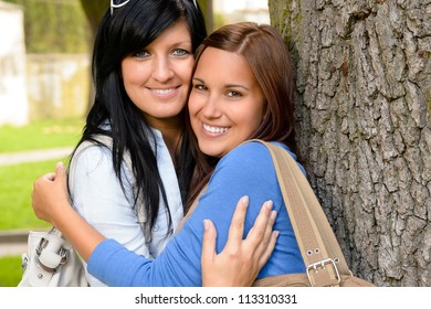 Mother and teen hugging outdoors relaxing smiling daughter bonding loving