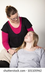 Mother and teenage daughter looking at each other friendly. Mother is standing behind the girl who is sitting down