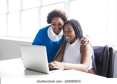 A Mother And Teenage Daughter Looking At Laptop Together