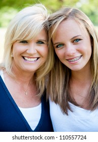 Mother and teenage daughter outside smiling