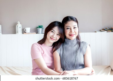 Mother and teenage daughter smiling at home