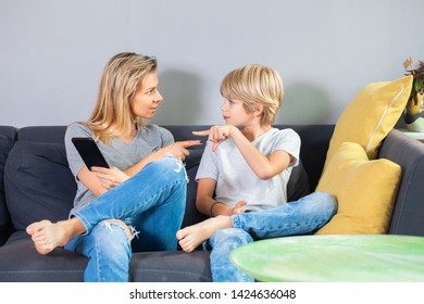 Mother And Teenage Son Arguing On Sofa At Home because she took his smartphone away from him.Family and modern technology addiction concept