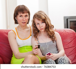 Mother and teenager daughter sitting on sofa together and listening mp3 players