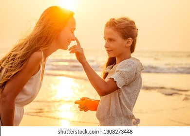 mother and teenager daughter using sunscreen on the beach