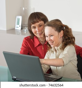 Mother and teenager girl with laptop computer together at home