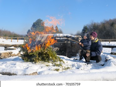 Mother and a three year old baby boy by a camping fire in a winter forest on a sunny day
