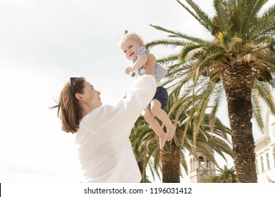 Mother throwing up an adorable baby girl under palm trees, family summer vacation concept