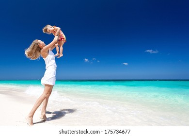 Mother throwing her daughter in air at the tropical beach