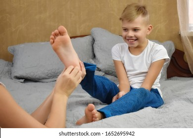 Mother tickles the child. Tickling and laughter. Mother and son together having fun. Mother touch baby son. Games with children at home