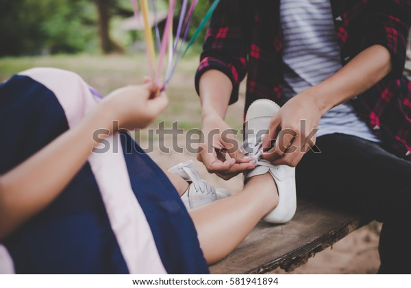 Mother tied shoe for her daughter while sitting on swing relaxing out doors together.